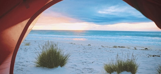 A student couple sleeping in a tent on the beach in Queensland are dreaming about the best city to live in Australia after their studies.