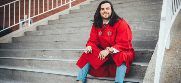 A college student is sitting on a stairway thinking about how to apply for scholarships for international students in Australia to finance his studies.