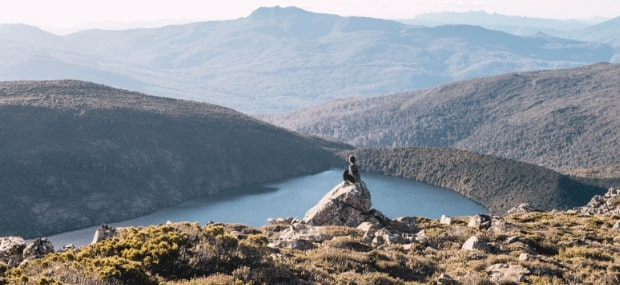 An international student in Hobart Tasmania is sitting on the tip of a mountain overlooking a valley and a bay.