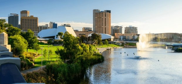 A sunny day in Adelaide South Australia with a fountain spraying in the air out of a river.
