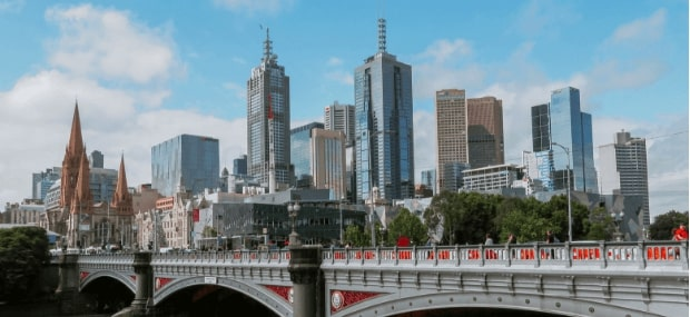International students are crossing a bridge behind colleges in Melbourne Australia after studying.
