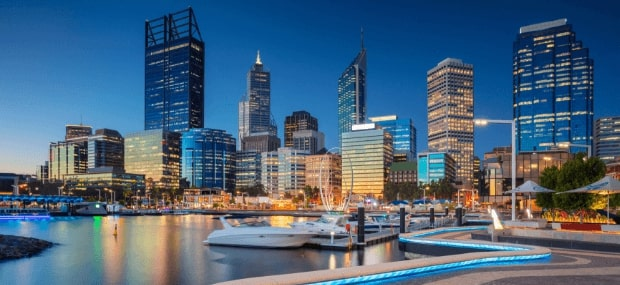 Perth, a popular student city in Western Australia, shining bright at night, with small boats parked in the harbour.