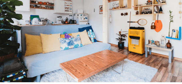 A cheap student accomodation in Sydney. A sofa, bed and table with a kitchen in the back.