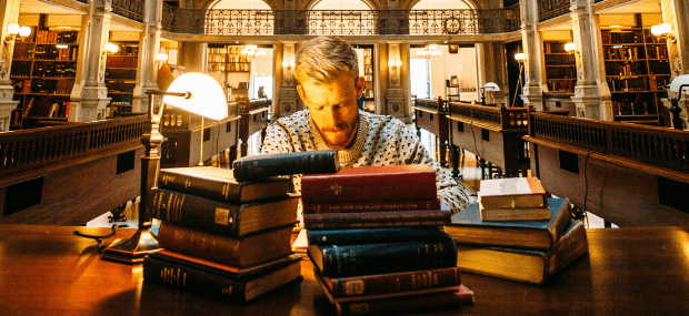 A graduate is reading about postgraduate study in Australia for international students inside a library.