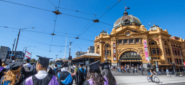 Graduates that studied the shortest bachelor degree in Australia are walking through Melbourne city.