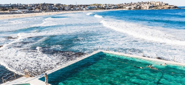A Sydney ocean pool in New South Wales with international students sunbathing, swimming and surfing.