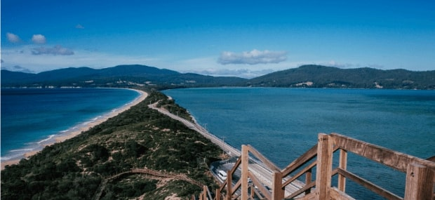 An international student in Tasmania is looking over the ocean after studying a course at university.