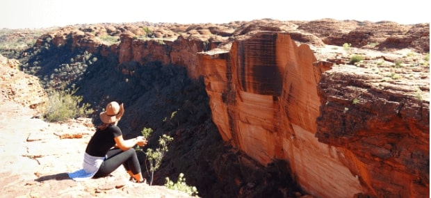 An International student studying in Australia sitting on a rock in the Northern Territory (NT) near to Darwin.