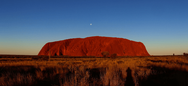 Uluru (Ayers Rock) shining red with a blue star sky during sunset.